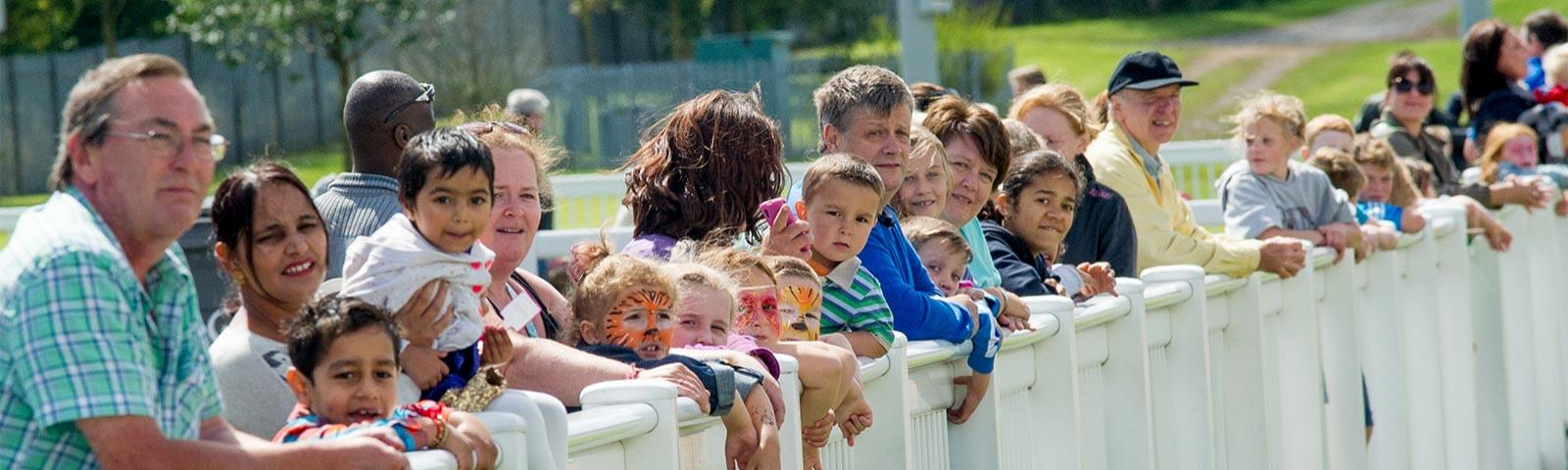 Families with face painted children gather to watch the race.