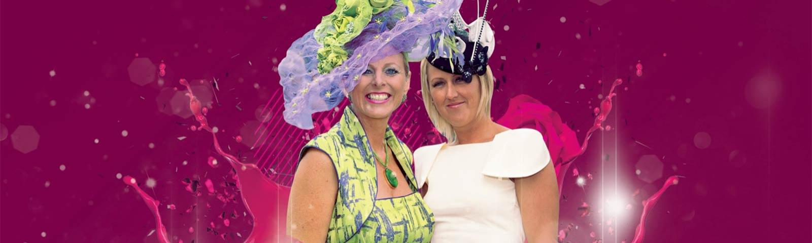 Two ladies dressed suitably for a Ladies Day racing event.  Including posh hats.
