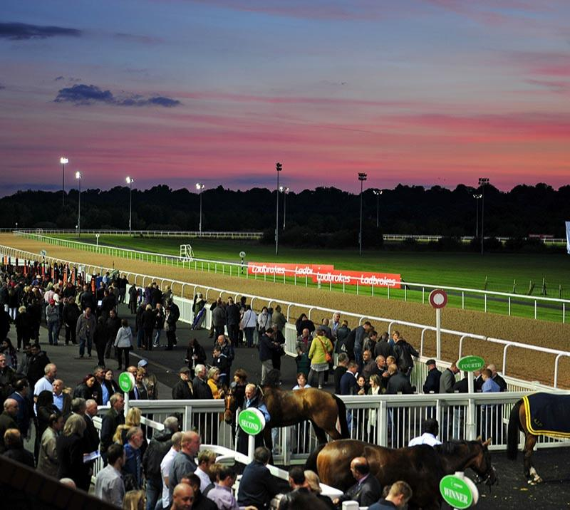 Crowds at a evening race meeting at Wolverhampton Racecourse.