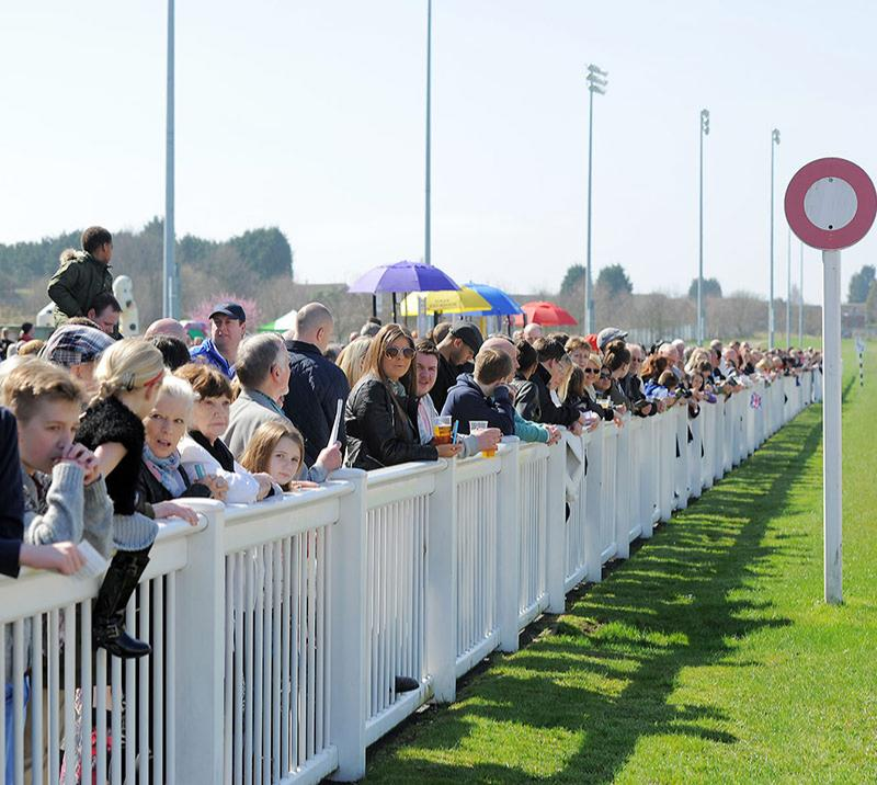 Crowds lined up against the track railing to watch the racing action up close.